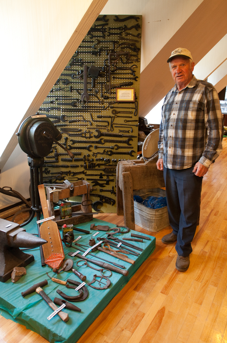Victor Tremblay stands beside tool collection Mattawa_Museum